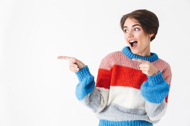Garota alegre e feliz vestindo um suéter isolado no branco, apontando o dedo para o espaço da cópia