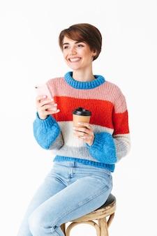 Garota alegre e feliz vestindo um suéter sentado em uma cadeira isolada no branco, usando um telefone celular, segurando um copo para viagem