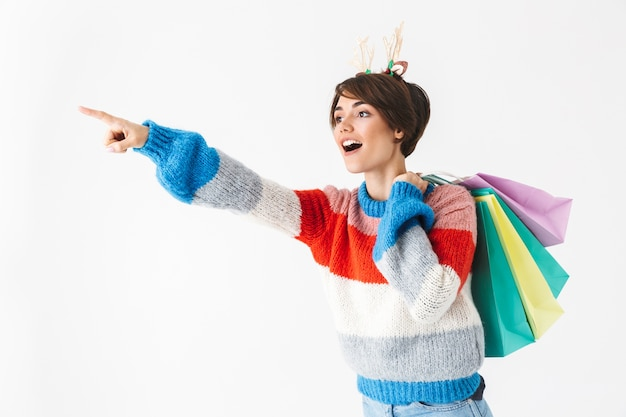 Garota alegre e feliz vestindo uma camisola em pé, isolada no branco, carregando sacolas de compras e apontando para longe