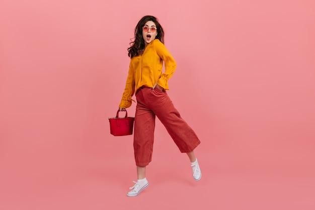 Garota alegre em óculos elegantes encara com espanto, andando na parede rosa. morena de culote e blusa laranja, posando com bolsa vermelha.