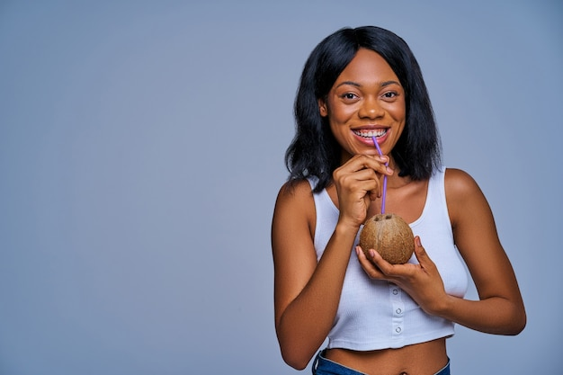 Garota alegre em top branco bebe de um coco por um canudo. conceito de dieta