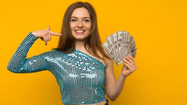 Garota alegre ganhou na loteria e apontando em um leque de dólares americanos em suas mãos em um fundo amarelo - imagem