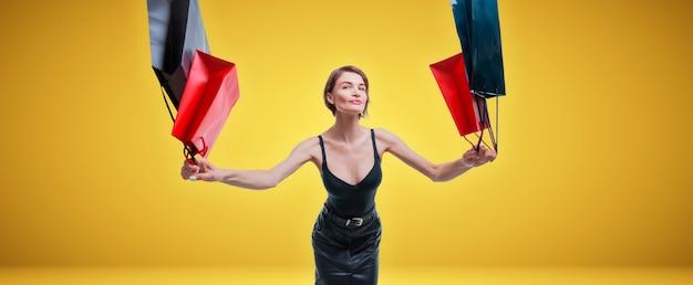 Garota alegre positiva pula de felicidade e acenando sacolas de compras. o conceito de presentes de natal, grandes descontos, vendas. mídia mista