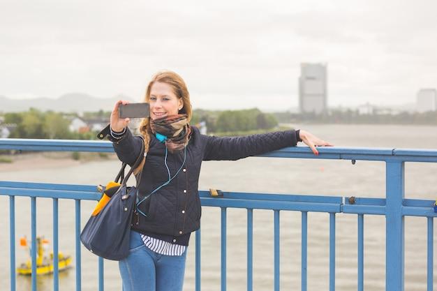Garota alemã tomando selfie em bonn com rhein em fundo