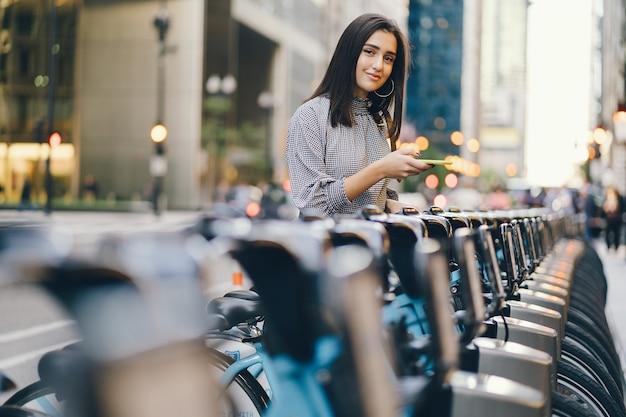 Garota alugando uma bicicleta da cidade de um stand de bicicleta