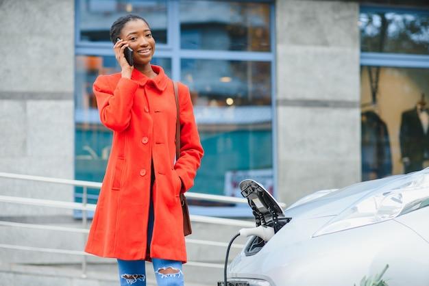 Garota americana em pé perto do carro.