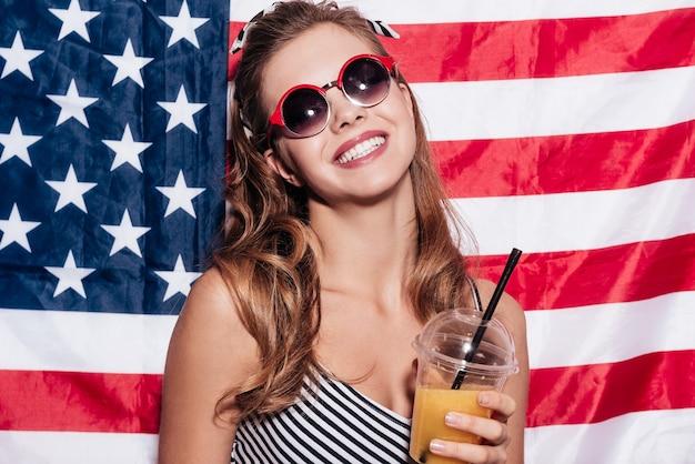 Garota americana. jovem alegre segurando uma xícara de suco e usando óculos escuros, enquanto fica de pé contra a bandeira nacional americana
