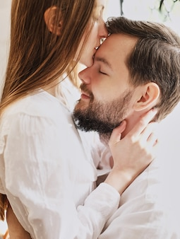 Garota amor beija o namorado na testa. abraçando gentilmente beijo. vestido de pijama