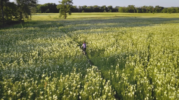 Garota andando de bicicleta no sol prado aéreo campo natureza paisagem esporte ativo florescer flores