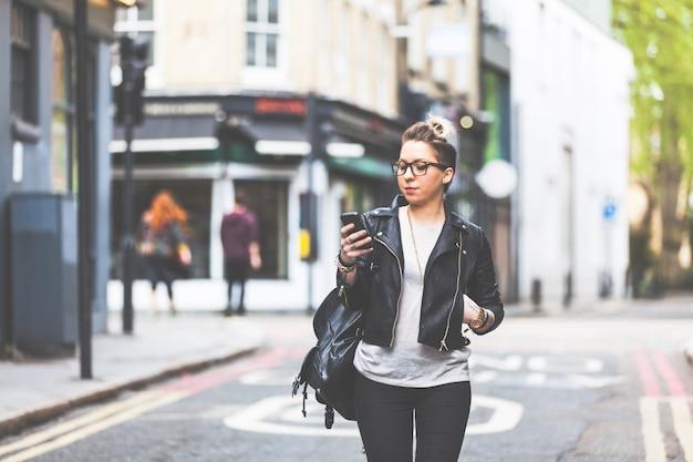Garota andando na rua com o telefone dela.