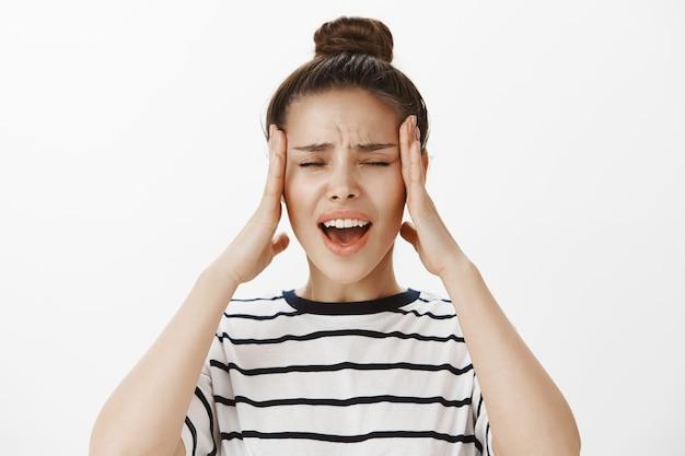 Garota angustiada e incomodada reclamando de dor de cabeça, esfregando tempels e fazendo caretas de frustração