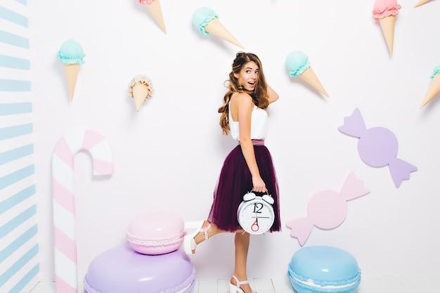 Garota animada carregando um grande relógio de pé em uma perna e olhando para longe. retrato de corpo inteiro de uma jovem inspirada usando uma saia longa roxa escura posando