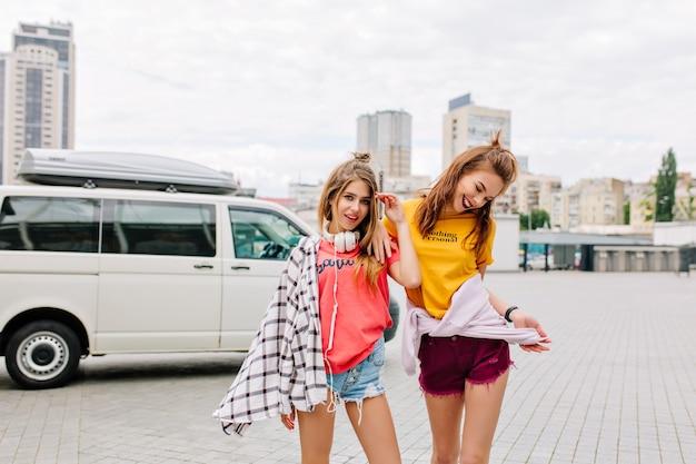 Garota animada com cabelo castanho dançando em shorts jeans e olhando para baixo com um sorriso
