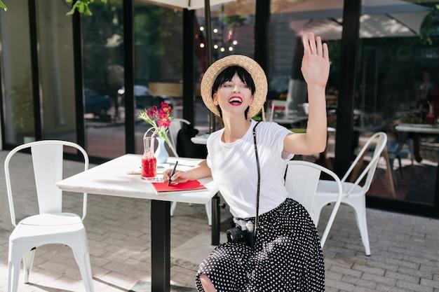 Garota animada com cabelo escuro curto acenando com a mão para alguém à distância enquanto trabalhava sozinha em um café ao ar livre