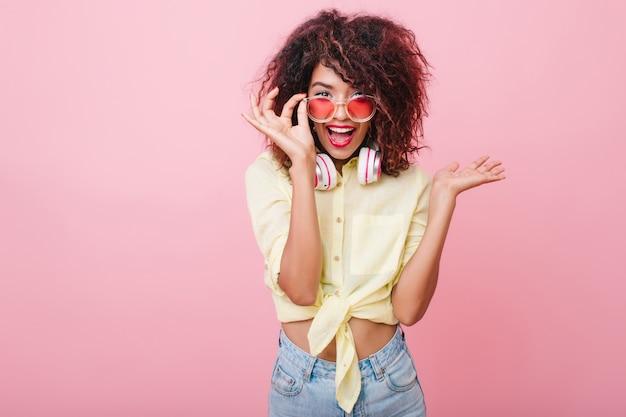 Garota animada com fones de ouvido coloridos posando com prazer e expressando emoções verdadeiras. senhora romântica com sorriso surpreso, segurando seus óculos de sol rosa.