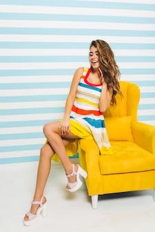 Garota animada com um penteado lindo olhando para longe, sentado na mobília amarela moderna na parede listrada. retrato de uma jovem sonhadora em um vestido da moda brilhante, tocando o cabelo com a mão.