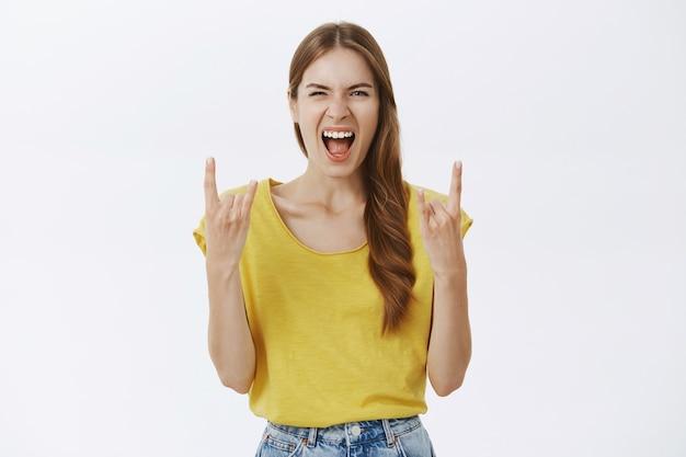 Garota animada e alegre se divertindo, mostrando gestos de rock-n-roll e curtindo show