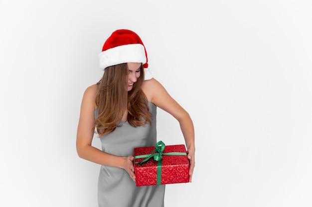 Garota animada e positiva com chapéu de papai noel sacudindo a caixa de presente enquanto fica na comemoração de fundo branco