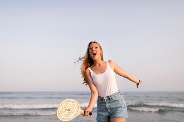Garota animada em frente a beira-mar jogando tênis