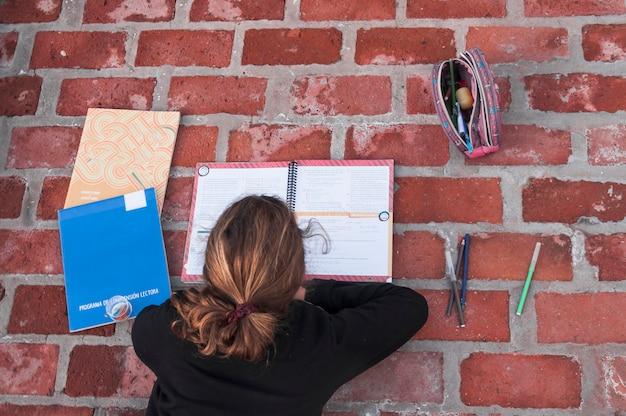 Garota anônima estudando no pavimento de tijolo