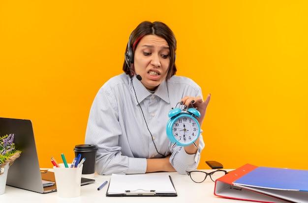Garota ansiosa de call center usando fone de ouvido, sentada na mesa, segurando e olhando para o despertador isolado em laranja