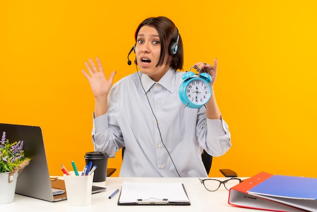 Garota ansiosa de call center usando fone de ouvido, sentada na mesa, segurando um despertador e mostrando a mão vazia isolada em laranja