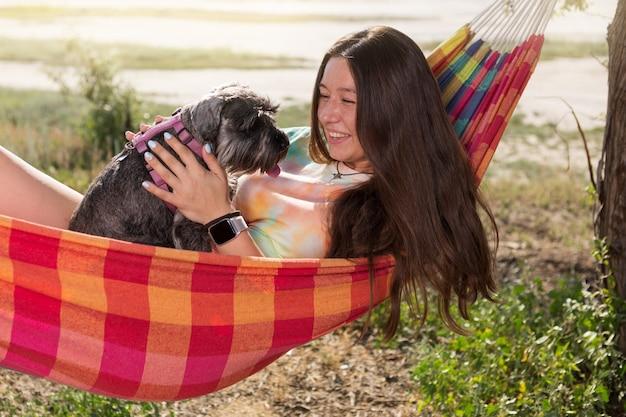 Garota ao ar livre, deita-se em uma rede e segura um cachorro schnauzer em miniatura nos braços, emoções, conceito