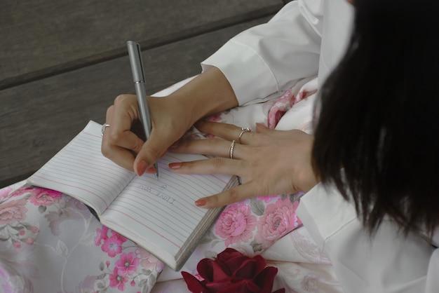 Garota apaixonada escreve uma carta em um caderno.