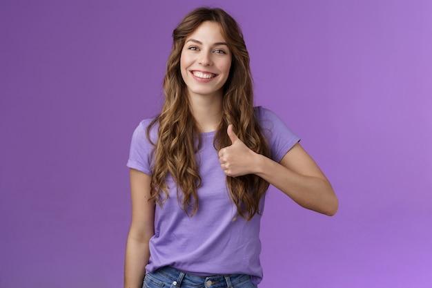 Garota apoiadora dá ao amigo uma resposta positiva polegar para cima sinal sorrindo amplamente satisfeita boa escolha grinn ...