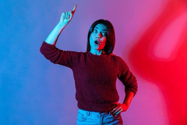 Garota apontando o dedo para cima com uma boa ideia e parecendo surpresa