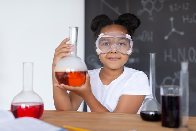 Garota aprendendo mais sobre química na aula