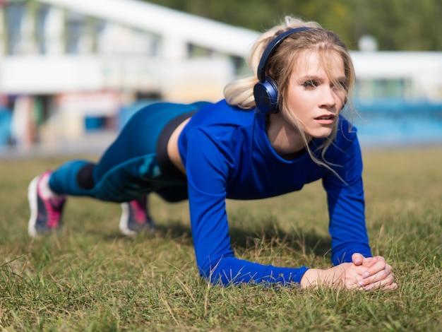 Garota apta em fones de ouvido fazendo exercício de prancha ao ar livre no parque dia quente de verão.