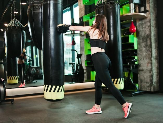 Garota apta no sportswear e trens de luvas de boxe soprar contra um saco de pancadas em um ginásio escuro.