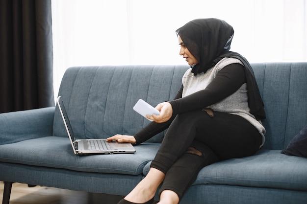 Garota árabe moderna em hijab usando laptop em casa, trabalhando remotamente enquanto está sentada no sofá da sala de estar