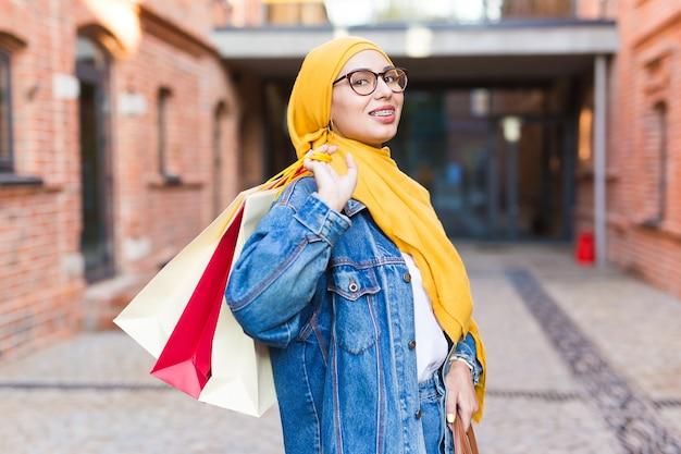 Garota árabe muçulmana feliz com sacolas de compras