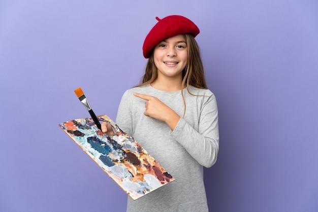 Garota artista em parede isolada apontando para o lado para apresentar um produto
