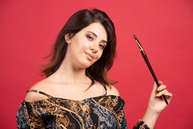 Garota artista posando com seu pincel de pintura.