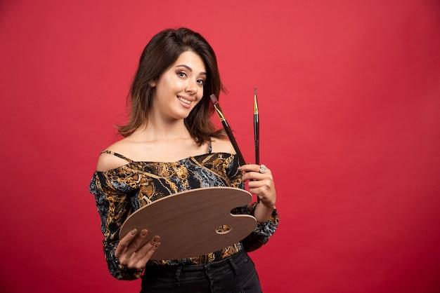 Garota artista posando com sua paleta de madeira e pincel.