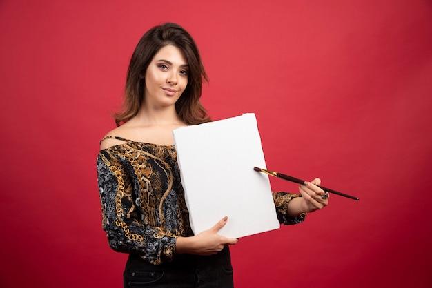 Garota artista segurando sua arte na tela e demonstrando-a ao público.
