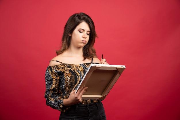 Garota artista segurando uma tela e parece pensativa ou sem inspiração.