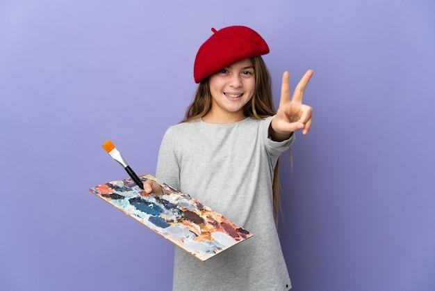 Garota artista sobre fundo isolado sorrindo e mostrando sinal de vitória