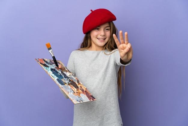 Garota artista sobre um fundo isolado feliz e contando três com os dedos