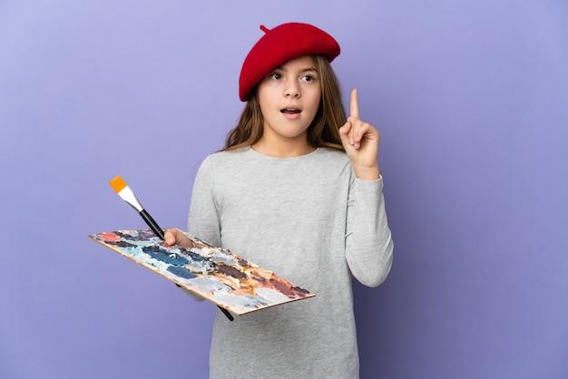Garota artista sobre um fundo isolado pensando em uma ideia apontando o dedo para cima