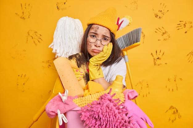 Garota asiática cansada e frustrada não quer limpar a sala cercada por muitas ferramentas de limpeza e detergentes olha tristemente para a câmera isolada sobre a parede amarela