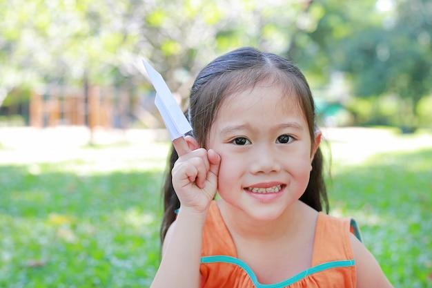 Garota asiática criança dobre um pedaço de papel branco para foguete e mostrando no dedo indicador em pa