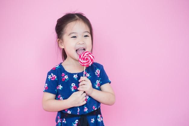 Garota asiática feliz comendo pirulito na cor rosa com espaço de cópia