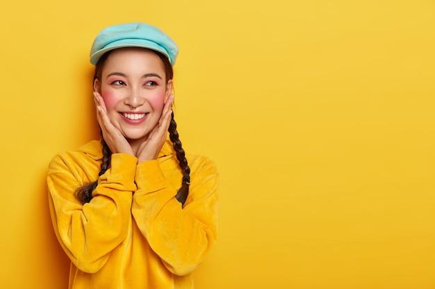 Garota asiática feliz toca bochechas ruge, usa maquiagem e piercing, boné estiloso e moletom de veludo, tem expressão sonhadora