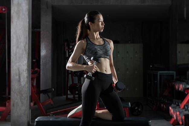 Garota asiática fitness com treino de corpo de forma perfeita, levantando um haltere no ginásio