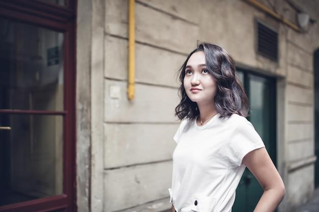 Garota asiática otimista em uma camiseta branca, olhando para cima