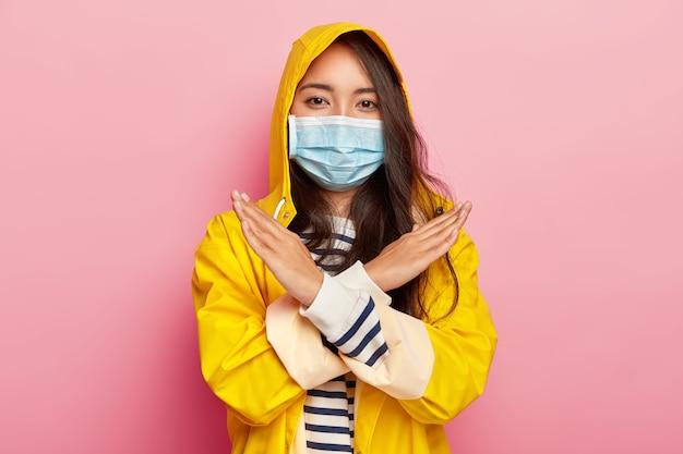 Garota asiática séria faz gesto de parar ou banir, tem doença infecciosa, mantém os braços cruzados, usa capa de chuva impermeável